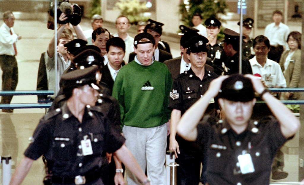Rogue financial trader Nick Leeson arrives at Singapore's Changi airport surrounded by local police officers on November 23, 1995